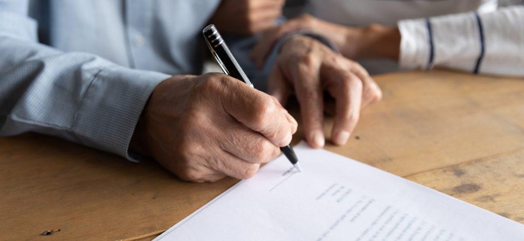 Nahaufnahme von Händen, die einen Vertrag unterschreiben