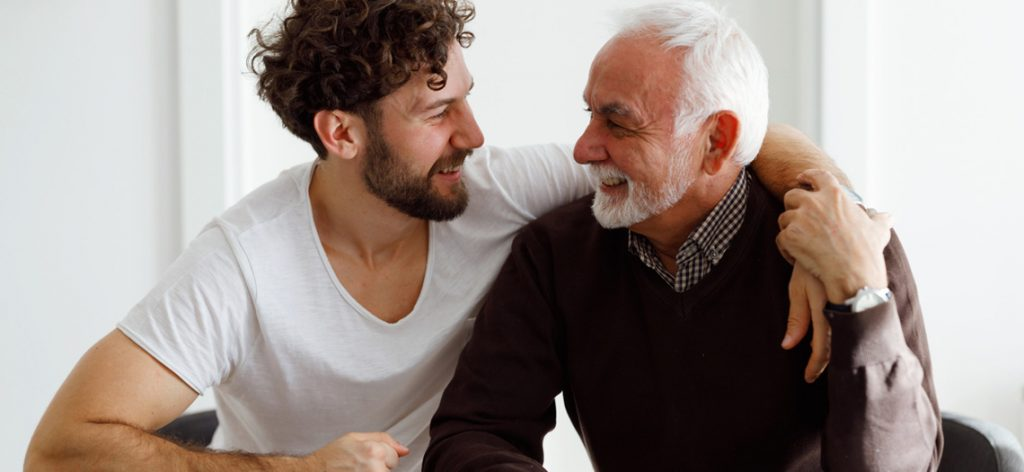 Junger Mann umarmt alten Mann und lacht