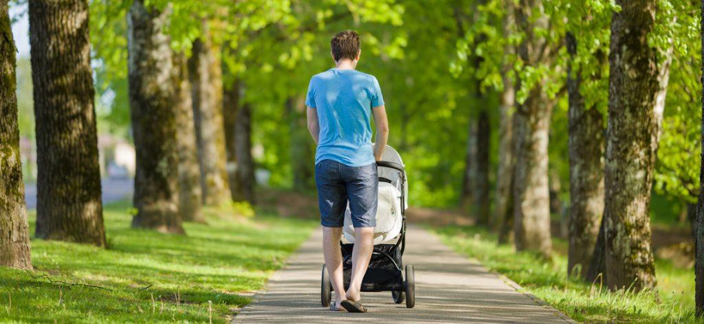 Junger Vater mit Kinderwagen
