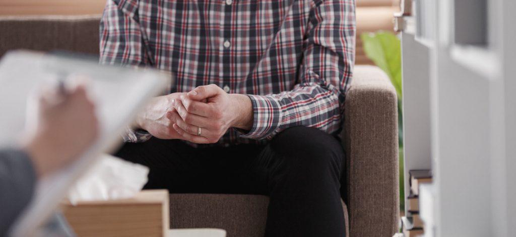 Nahaufnahme eines Mannes, der auf dem Sofa sitzt und die Hände faltet.
