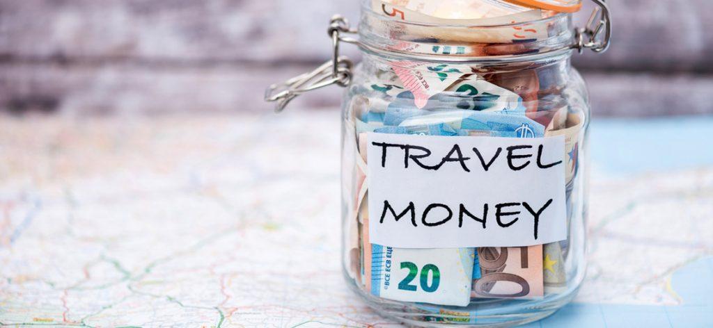 """Mit Geld gefülltes Glas auf dem """"Reisekasse"""" steht"""