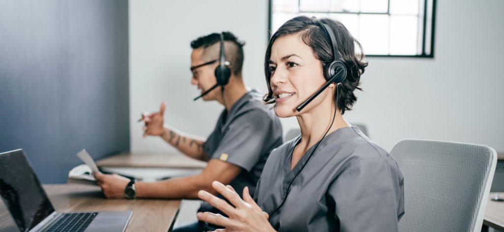 Eine Frau und ein Mann telefonieren jeweils mit Headset
