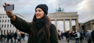 Frau macht Selfie von sich vor dem Brandenburger Tor