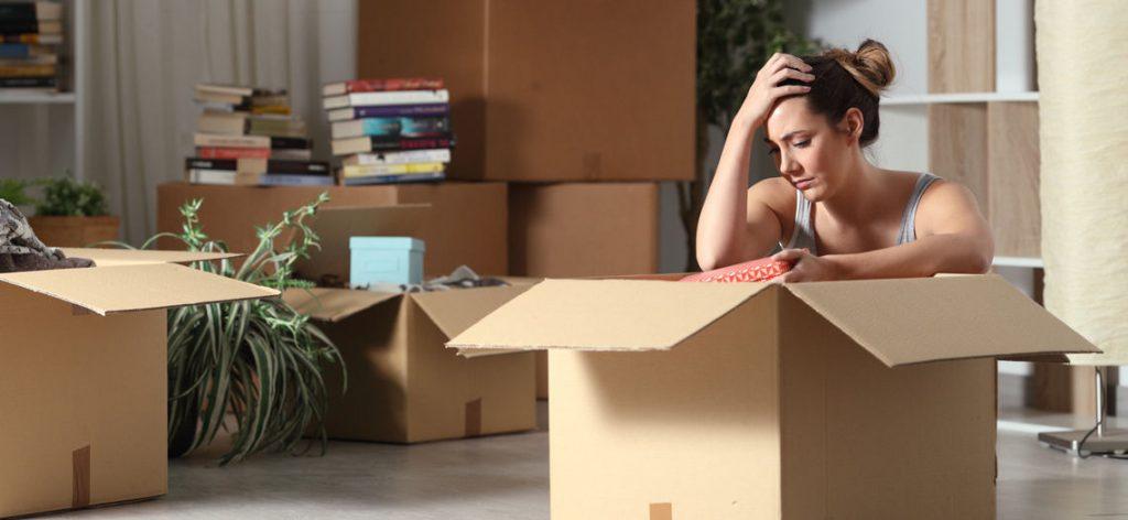 Frau sitzt traurig über Umzugskartons