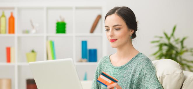 junge Frau mit Kreditkarte in der Hand sitzt vor dem Laptop