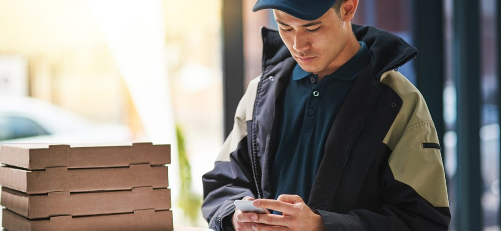 Junger Pizza-Bote schaut auf sein Handy