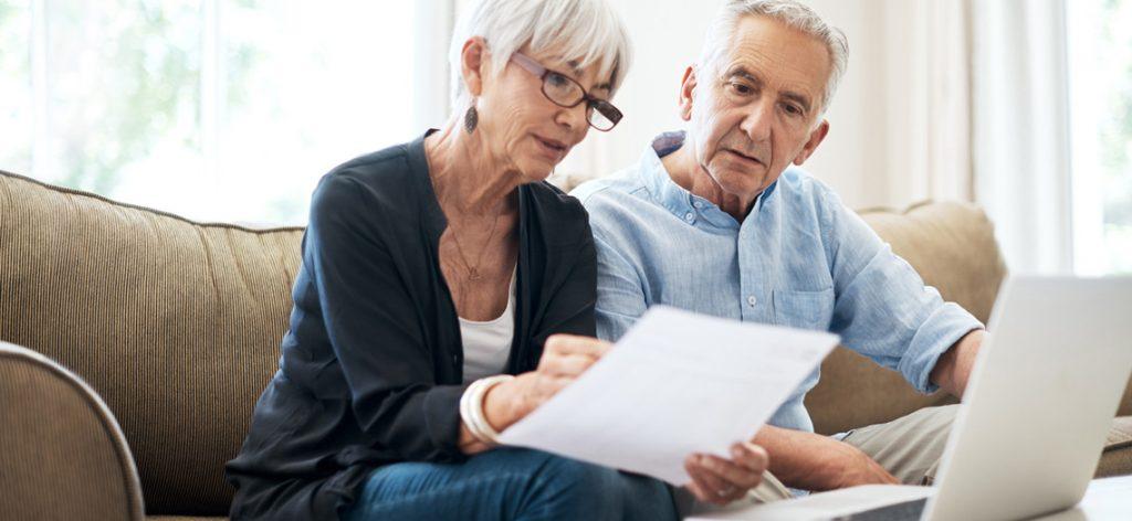 Älteres Paar studiert gemeinsam Unterlagen