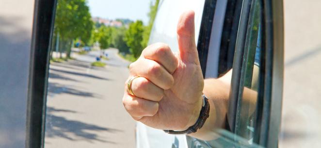 Autofahrer hält Faust mit Daumen hoch aus dem Autofenster