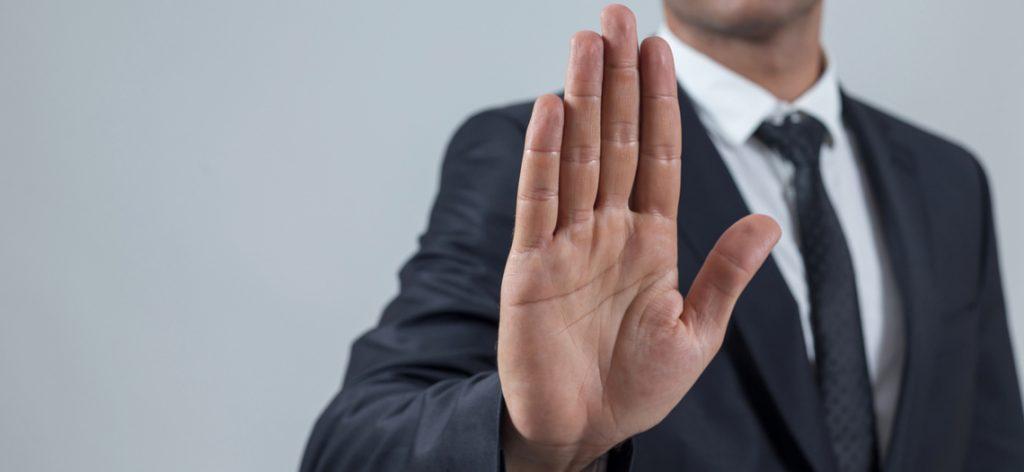 """Mann im Anzug zeigt mit der Hand """"Stopp"""""""