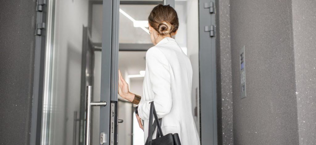 Junge Frau verlässt ein modernes Bürogebäude