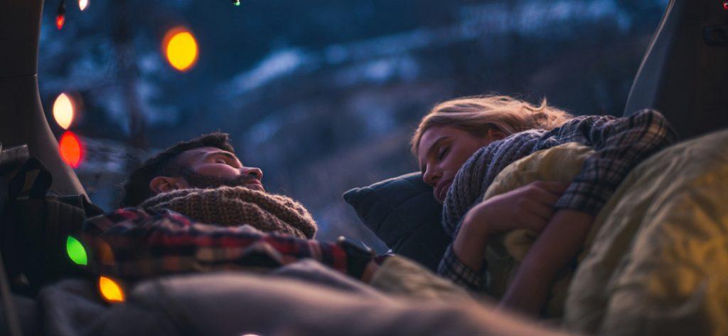 Junges Paar schläft im Van unter einer Lichterkette im Freien