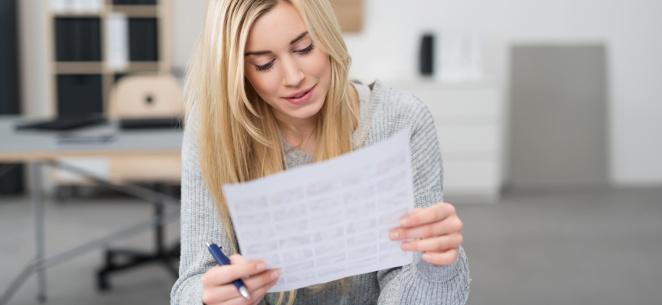 Frau schaut interessiert auf das Kleingedruckte eines Dokuments