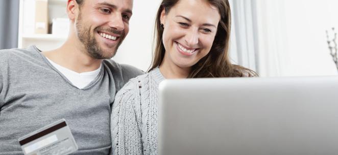 junges Paar sitzt lächelnd vor einem Computer, Mann hält eine Kreditkarte in der Hand