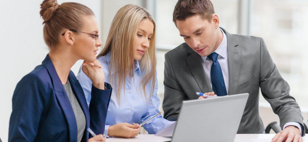 Drei Arbeitnehmer gucken auf einen Laptop