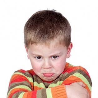 Koerpersprache deuten: beleidigtes Kind mit verschränkten Armen