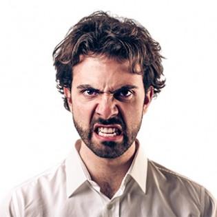 Koerpersprache deuten: Mann mit boesem Blick und gefletschten Zaehnen