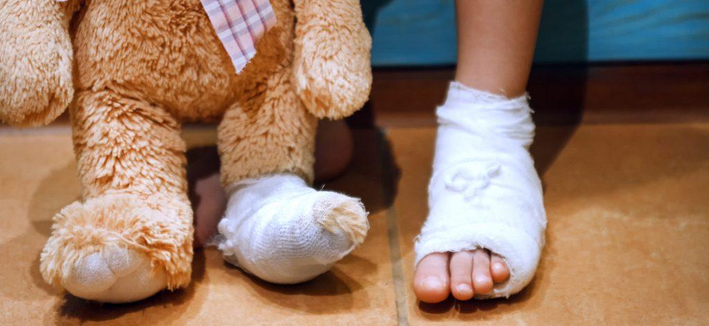 Kinderfuß mit Verband. Daneben ein Teddybein, ebenfalls mit Verband
