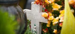 Grabgestaltung: Ein graues Kreuz umrankt von Blumen.