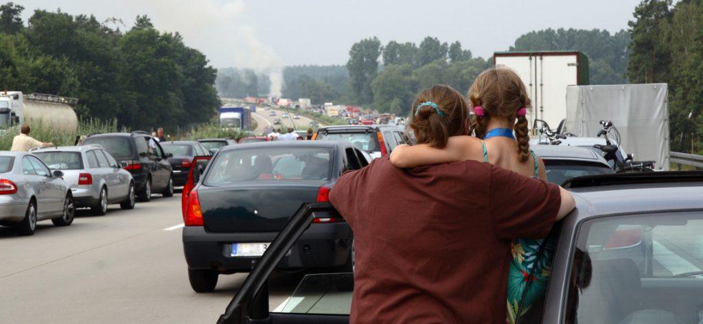 Frau hält Kind im Arm und schaut auf die Fahrbahn