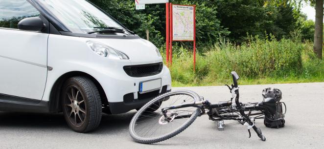 Fahrradunfall: Unachtsamer Radfahrer trägt Alleinschuld. Neben einem weißen Smart liegt ein Rad auf dem Asphalt.