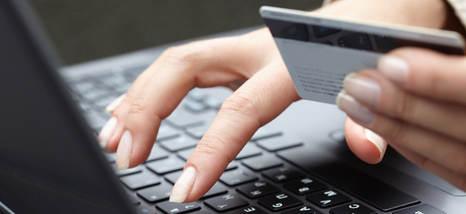 Fake-Shops: Schutz vor Betrug mit Thermomix und Co. Ein Frau hält eine Geldkarte in der einen Hand und tippt mit der anderen Hand auf einem schwarzen Laptop.