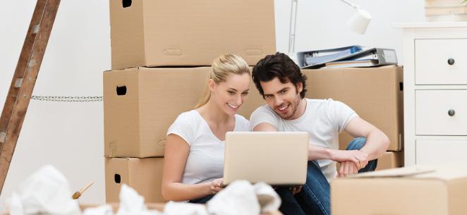 Sonderurlaub bei Umzug: Diese Rechte haben Sie. Ein junges Paar sitzt zwischen Umzugskartons und schaut auf einen Laptop.
