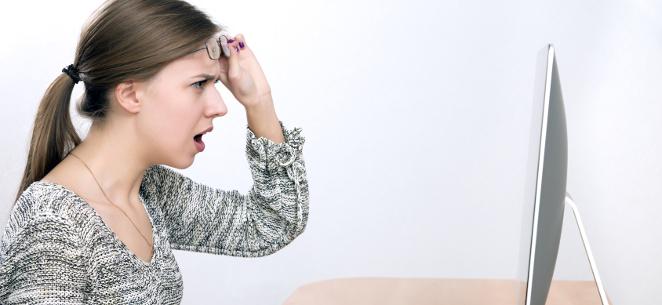 E-Mail-Konto gehackt: Spam-Mails vom eigenen Konto. Eine Frau sitzt entsetzt vor einem Bildschirm und schiebt sich entsetzt die Brille auf die Stirn.