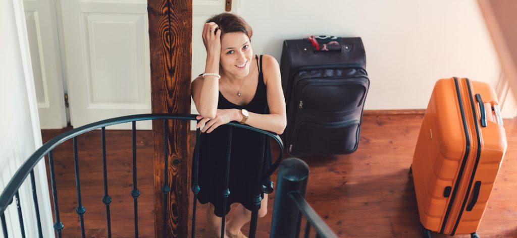 Frau steht am Geländer mit gepackten Koffern