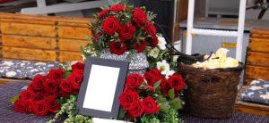 Seebestattung: Ablauf und Rechtslage. Um eine Urne sind drei Gestecke aus roten Rosen drapiert.