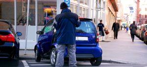 """""""Wegeheld"""" und Co.: Rechtliches zur Falschparker-App. Ein Mann vom ordnungsamt steht vor einem blauen Smart der in einer Halteverbotszone steht."""