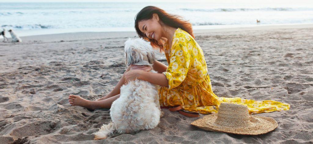 Frau sitzt mit ihrem Hund am Strand und lacht