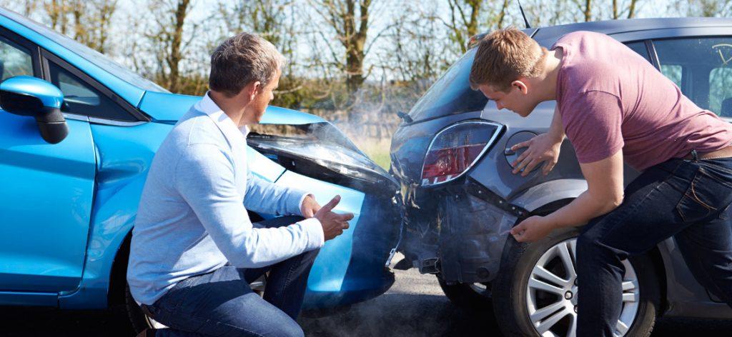 Anscheinsbeweis bei Auffahrunfall: Klärung der Schuldfrage. Zwei Männer stehen vor Ihren Autos, die aufeinander gefahren sind.
