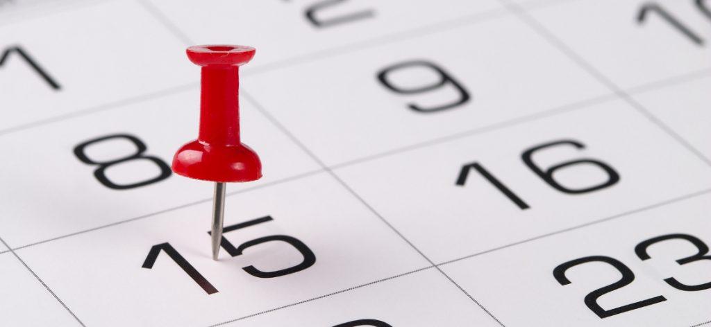 """Eine rote Pin-Nadel steckt in der """"15"""" auf einem Kalenderblatt."""
