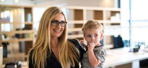 Elternzeit verkürzen: Ihre Rechte als Arbeitnehmer. Ein Frau mit langen blonden Haaren und Brille trägt einen kleinen Jungen auf dem Arm.