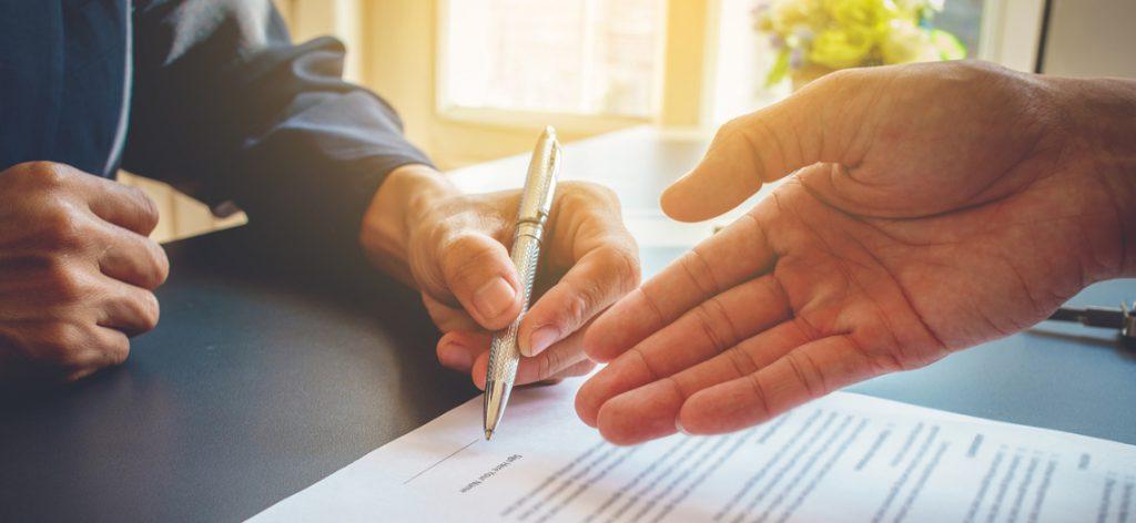 Nahaufnahme wie ein Vertrag unterschrieben wird und eine andere Hand erhebt Einspruch