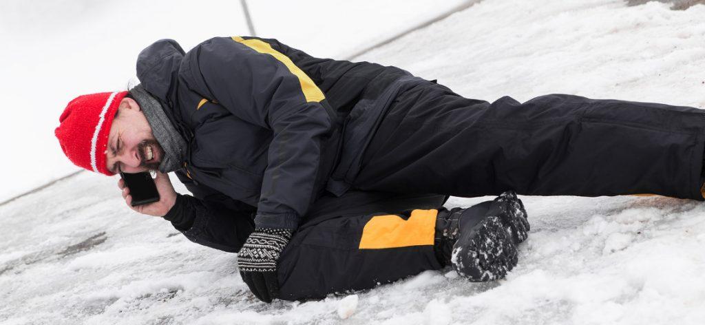 Glätteunfall auf dem Gehweg: Beweislast und Schmerzensgeld. Ein Mann liegt im Schnee, er hält sich mit deiner Hand das Knie. In der anderen Hand hält er ein Handy.