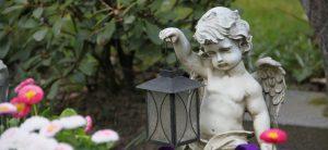 Familiengrab: Diese rechtlichen Möglichkeiten gibt es. Ein steinerner Engel mit einer Lampe in der Hand.