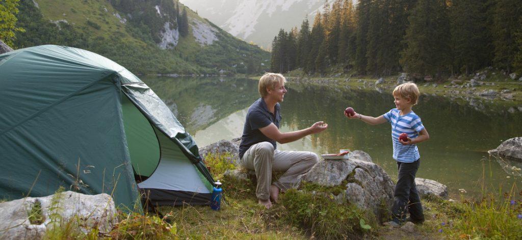 Vater und Sohn campen gemeinsam an einem See