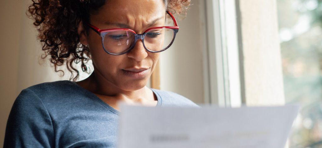 Frau schaut besorgt auf Mietvertrag