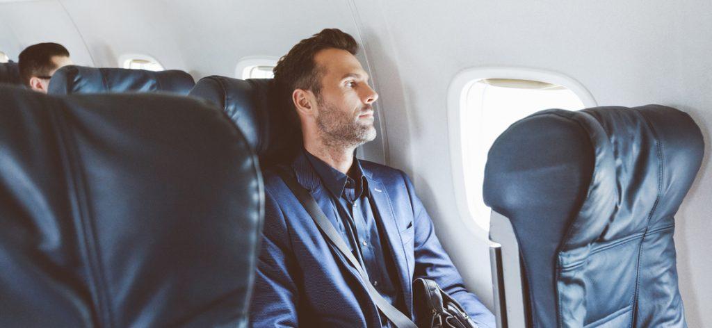 Mann im Flugzeug schaut verträumt aus dem Fenster
