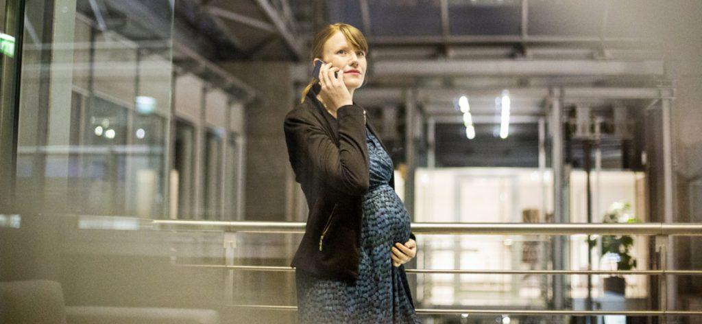 Schwangere Frau im Business-Dress telefoniert in einer Lagerhalle