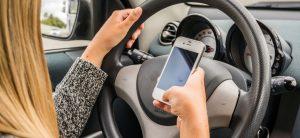 Frau am Steuer mit Handy