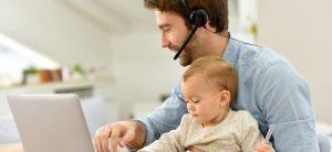 Man sitzt mit Headset vor dem Laptop und hat ein Baby auf dem Schoß
