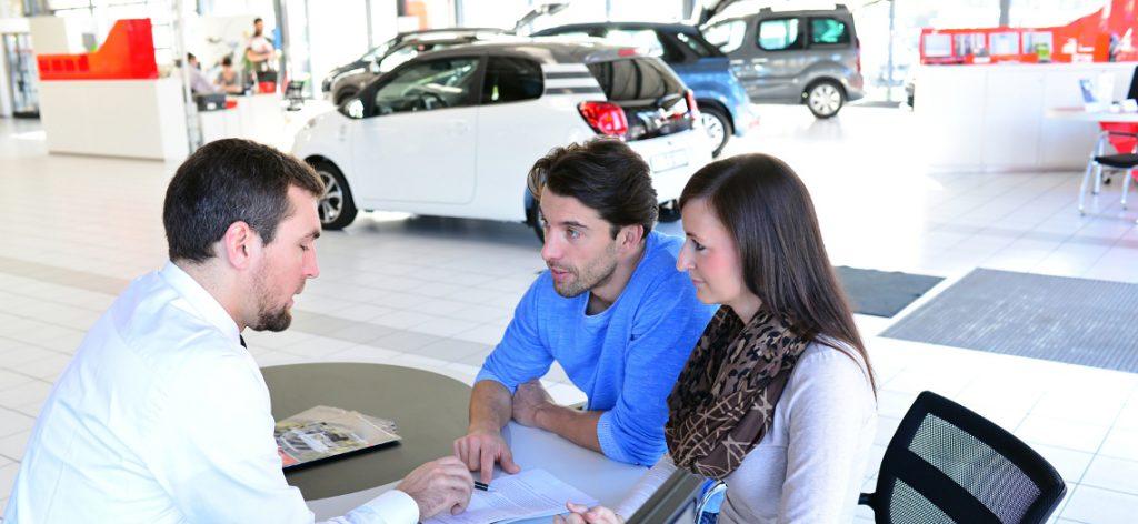 Eine Frau und ein Mann sitzen mit einem Autoverkäufer an einem Tisch
