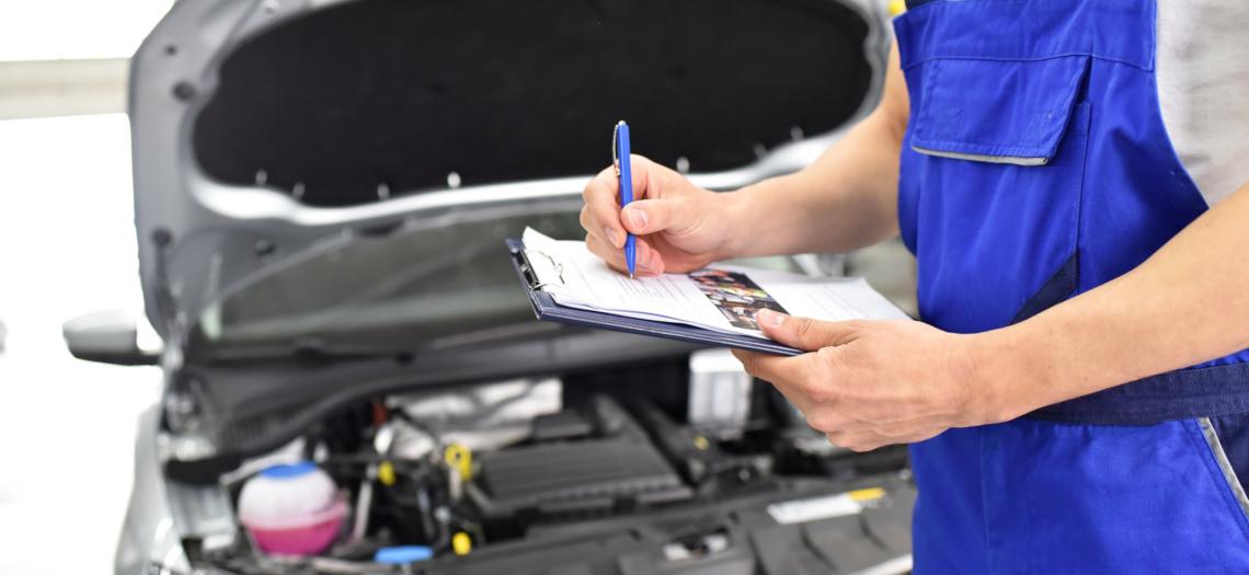 Ein Mann steht vor einem Auto mit geöffneter Motorhaube und hakt eine Liste ab
