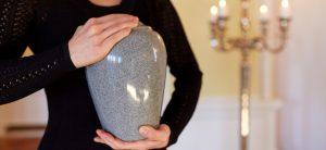 Person hält Urne mit beiden Händen vor der Brust.