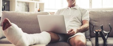 Mann sitzt mit Gips-Bein auf dem Sofa