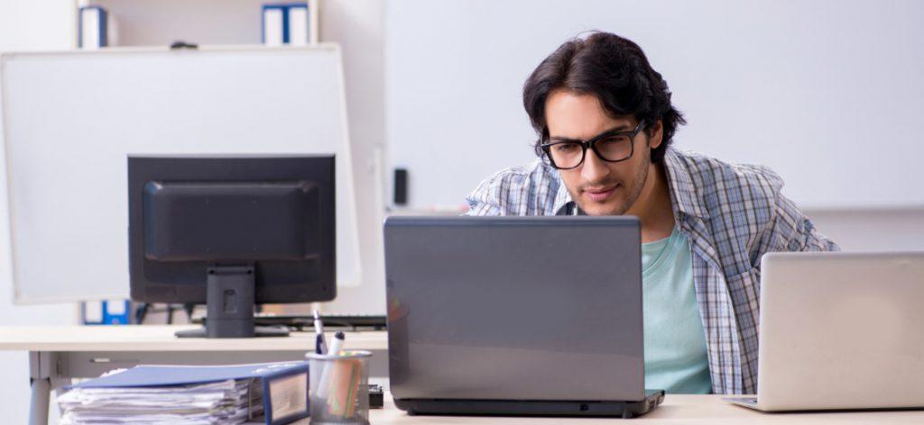 Mann sitzt vor dem Laptop