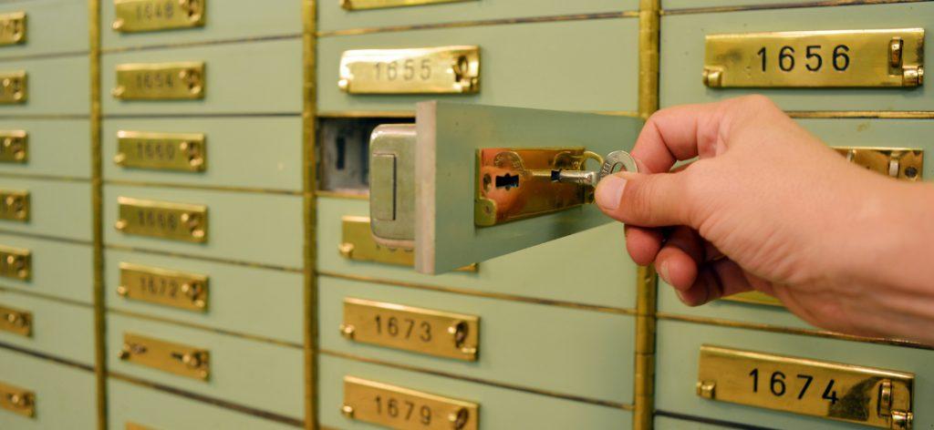 Hand schließt ein Schließfach mit dem Schlüssel auf