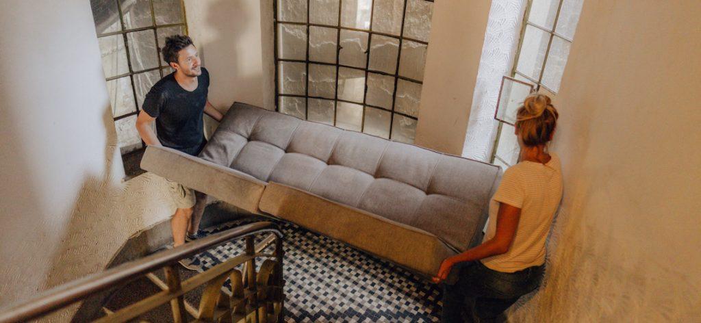 Junges Paar trägt Couch eine Treppe hoch